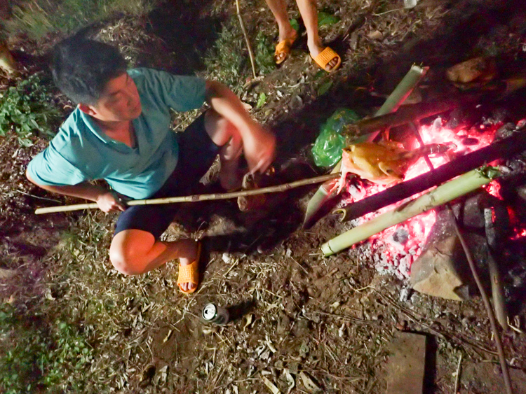 Our Easy Rider Vietnam guide cooking chicken on fire