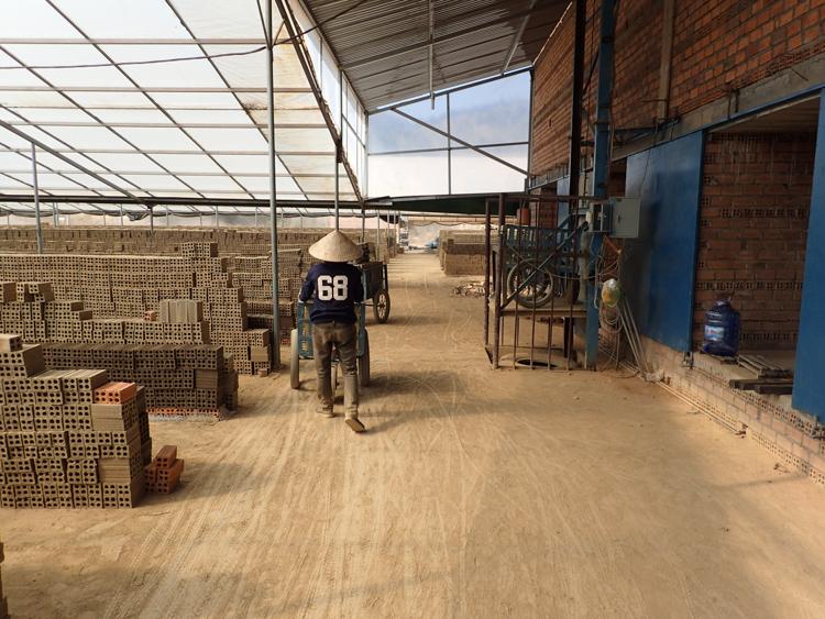 Man moving bricks in brick factory